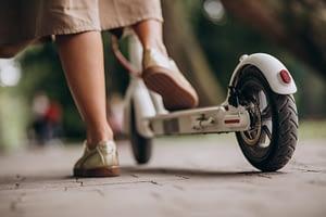 Chica montando en patinete electrico de Xiaomi en un parque